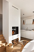 Fire in white fireplace with firewood store in modern interior