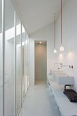Narrow, white washing area with twin sinks and pendant lamps opposite floor-to-ceiling glass panels