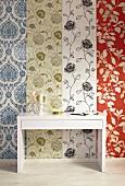 Weisser, moderner Konsolentisch vor tapezierter Wand mit Mustermix-Tapetenstreifen