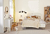 Bedspread with smocked diamond pattern on double bed in bedroom painted pale yellow; white console table against wall