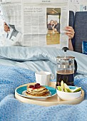 Breakfast tray of coffee and waffles in front of person reading newspaper in bed