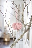 Pink paper pompom on bare branch