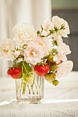 Summer bouquet of white garden roses and sprigs of strawberries in glass vase