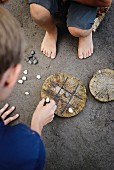 Noughts and crosses game played by children using pebbles and game board on disc of wood