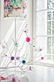 White branches decorated with colourful pompoms decorating table in front of standard lamp with colourful lampshade