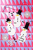 Festive, hand-made snowman decorations on geometric wrapping paper