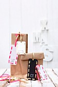 Hand-made festive gift tags with decorative letters on gift bags
