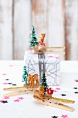 Clothes pegs decorated with tiny deer figurines and Christmas trees