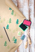 Hand-crafted wrapping paper made from brown paper printed with pattern of Christmas trees