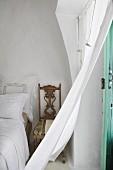 Curtain wafting in breeze in Mediterranean bedroom