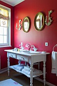 Vintage-style washstand against red wall