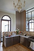 Küchenzeile übereck mit Edelstahlfronten vor Brüstungswand