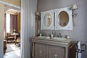 Eleganter Waschtisch mit zwei eingelassenen Waschbecken vor gerahmten, runden Spiegeln neben Durchgang mit Vorhang