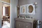 Elegant washstand with twin inset sinks below round mirrors next to curtain in doorway