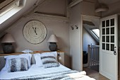 Double bed and vintage clock in attic bedroom with view of stairwell through open door