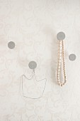 Hand-made concrete wall hooks, one with string of wooden beads