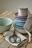 Stacked plates, scissors and linen ribbon