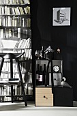 Monochrome interior with drinks cabinet, stool and photo mural of bookcase