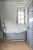 Free-standing bathtub and heated towel rail in farmhouse