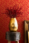 Twigs of red berries in gold vase on fur-covered stool