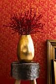 Rote Beerenzweige in Goldvase auf Fellhocker