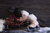 Winter still-life arrangement of old ice skates, sledge made of branches and artificial snow