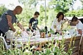 Blick über Grünpflanze auf Familie beim Brunch vorbereiten in sommerlichem Garten