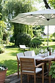 Set table below parasol in neat garden