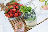 Refreshing drink with herbs in glass jug and glass dish of fresh berries