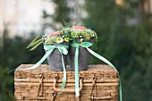 Flower arrangements in pots tied with satin ribbons on wicker trunk