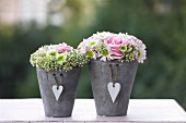 Flower arrangements with roses in grey pots with heart-shaped pendants