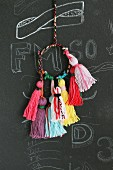 Colourful woollen tassels for key chains hanging against chalkboard