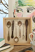 Cutlery mounted in wooden box in front of modern portrait on canvas