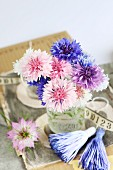 Posy of pastel cornflowers in glass vase decorated with tassels