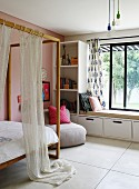 Canopied bed with wooden frame next to shelves and window seat in modern, child's bedroom