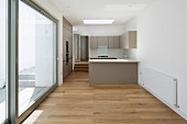 Long, unfurnished apartment with open-plan kitchen