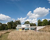 Modern architect-designed house with flat roofs and large windows seen across meadow