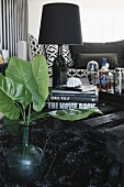Green leaves in glass vase in front of stacked books and black table lamp on table made from pallet