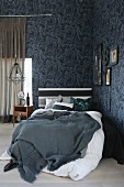 Bed with grey blanket and white bed linen in corner of masculine room with floral wallpaper