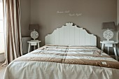 Double bed with white, ornate wooden headboard against taupe wall in elegant bedroom