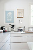 Electrical appliances on L-shaped kitchen counter with white base units below framed posters on wall