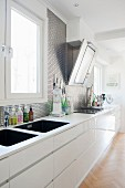 Long white kitchen counter with twin sinks and metallic wall tiles