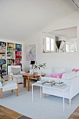 Delicate side table, white sofa, round wooden table and opening in internal wall in modern living area