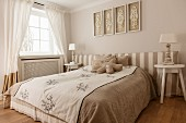 Double bed, striped upholstered headboard against wall and table lamp on bedside table in bedroom
