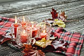 Red candles in glass lanterns and autumn leaves on tartan cloth