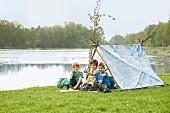 Selbst gebautes Zelt am Fluss mit Kindern