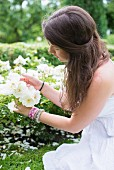 Young woman looking at white roses in garden