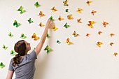 Junge Frau dekoriert Wand mit bunten Schmetterlingen