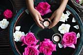 Schwimmende Rosenblüten und Teelichter in Keramikschale, Mädchenhände halten pinkfarbene Blüte