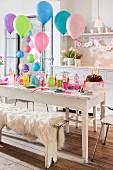 Festlich gedeckter Tisch und bunte Luftballons zum Kindergeburtstag
